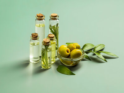Olive oil and olive branch on the green wooden table and green background